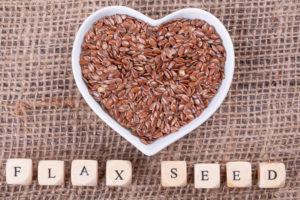 Flax seed in cup in the shape of heart on sack cloth